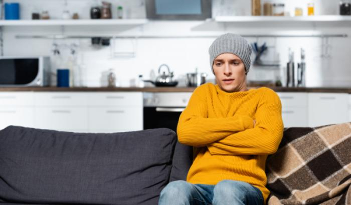 Person sitting on couch with hat, freezing.